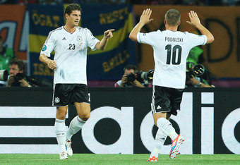 KHARKOV, UKRAINE - JUNE 13: Mario Gomez (L) of Germany celebrates with his team mate Lukas Podolski after scoring his team's first goal during the UEFA EURO 2012 group B match between Netherlands and Germany at Metalist Stadium on June 13, 2012 in Kharkov