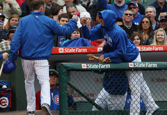 CHICAGO, IL - MAY 13:  Matt Garza #17 of the Chicago Cubs (R) playfully jumps over a teammate to congratulate Ryan Dempster #46 after Demster scored a run against the San Francisco Giants at Wrigley Field on May 13, 2011 in Chicago, Illinois.  The Cubs de