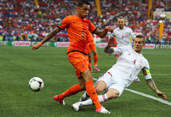 KHARKOV, UKRAINE - JUNE 09: Gregory van der Wiel of Netherlands and Daniel Agger of Denmark compete for the ball during the UEFA EURO 2012 group B match between Netherlands and Denmark at Metalist Stadium on June 9, 2012 in Kharkov, Ukraine.  (Photo by Ia