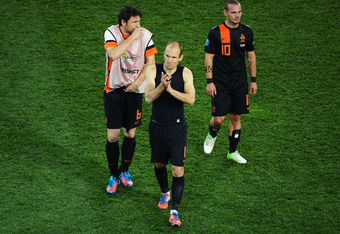 KHARKOV, UKRAINE - JUNE 17:  (L-R) Mark van Bommel, Arjen Robben and Wesley Sneijder of Netherlands show their dejection as he walks off the pitch after the UEFA EURO 2012 group B match between Portugal and Netherlands at Metalist Stadium on June 17, 2012
