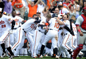 BALTIMORE, MD - JUNE 10:  Adam Jones #10 of the Baltimore Orioles celebrates scoring  the game winning run off a double by Matt Wieters #32 with Mark Reynolds #12 (L) and Steve Pearce #51 (R) during the tenth inning of an interleague baseball game against