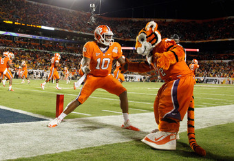 MIAMI GARDENS, FL - JANUARY 04:  Tajh Boyd #10 of the Clemson Tigers celebrates with the Clemson mascot after he threw a 27-yard touchdown pass to Sammy Watkins #2 in the first quarter against the West Virginia Mountaineers during the Discover Orange Bowl