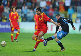 PODGORICA, MONTENEGRO - OCTOBER 07: Wayne Rooney of England kicks Miodrag Dzudovic of Montenegro before being sent off during the UEFA EURO 2012 group G qualifier match between Montenegro and England at the Gradski Stadium on October 7, 2011 in Podgorica,