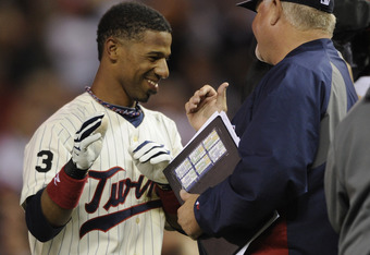 MINNEAPOLIS, MN - JUNE 9: Alexi Casilla #12 and manager Ron Gardenhire #35 of the Minnesota Twins celebrate a walk off hit by Casilla following their game against the Texas Rangers on June 9, 2011 at Target Field in Minneapolis, Minnesota. Twins defeated