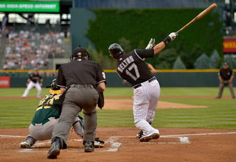 DENVER, CO - JUNE 13:  Todd Helton #17 of the Colorado Rockies follows through on his grand slam home run off of starting pitcher Tommy Milone #57 of the Oakland Athletics as catcher Josh Donaldson #20 of the Oakland Athletics backs up the plate and umpir