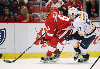DETROIT, MI - APRIL 15: Justin Abdelkader #8 of the Detroit Red Wings tries to control the puck in front of Gabriel Bourque #57 of the Nashville Predators during Game Three of the Western Conference Quarterfinals during the 2012 NHL Stanley Cup Playoffs a