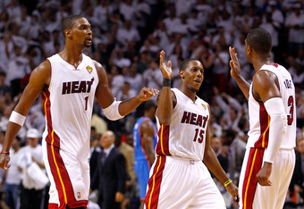 MIAMI, FL - JUNE 19:  (L-R) Chris Bosh #1, Mario Chalmers #15 and Dwyane Wade #3 of the Miami Heat celebrate in the fourth quarter against the Oklahoma City Thunder in Game Four of the 2012 NBA Finals on June 19, 2012 at American Airlines Arena in Miami,