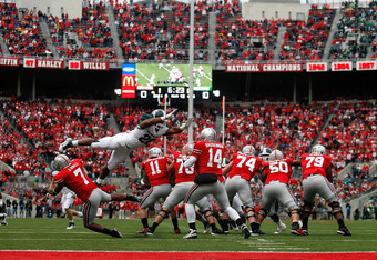 COLUMBUS, OH - OCTOBER 1:  Denicos Allen #28 of the Michigan State Spartans leaps over Jordan Hall #7 of the Ohio State Buckeyes on his way to sacking Joe Bauserman #14 of the Ohio State Buckeyes on October 1, 2011 at Ohio Stadium in Columbus, Ohio. Michi