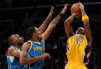LOS ANGELES, CA - APRIL 26:  Kobe Bryant #24 of the Los Angeles Lakers shoots over Trevor Ariza #1 and Emeka Okafor #50 of the New Orleans Hornets in the first quarter in Game Five of the Western Conference Quarterfinals in the 2011 NBA Playoffs on April