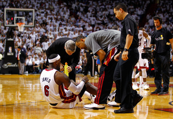 MIAMI, FL - JUNE 19:  LeBron James #6 of the Miami Heat is tended to by medical staff and teammates Juwan Howard #5 while he suffered from cramping in the second half against the Oklahoma City Thunder in Game Four of the 2012 NBA Finals on June 19, 2012 a