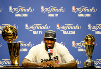 MIAMI, FL - JUNE 21:  LeBron James #6 of the Miami Heat answers questions from the media next to the Larry O'Brien Finals Championship trophy and James' Bill Russell Finals MVP trophy during his post game press conference after they won 121-106 against th