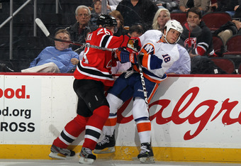 NEWARK, NJ - APRIL 03: Patrik Elias #26 of the New Jersey Devils hits Micheal Haley #18 of the New York Islanders into the boards at the Prudential Center on April 3, 2012 in Newark, New Jersey. The Devils defeated the Islanders 3-1.  (Photo by Bruce Benn