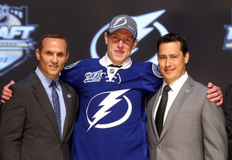 PITTSBURGH, PA - JUNE 22:  Slater Koekkoek (C), tenth overall pick by the Tampa Bay Lightning, poses on stage with general manager Steve Yzerman (L) and team representatives during Round One of the 2012 NHL Entry Draft at Consol Energy Center on June 22,