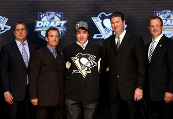 PITTSBURGH, PA - JUNE 22:  Derrick Pouliot (C), eighth overall pick by the Pittsburgh Penguins, poses with team co-owner Mario Lemieux (2nd R) and other team representatives on stage during Round One of the 2012 NHL Entry Draft at Consol Energy Center on