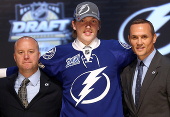 PITTSBURGH, PA - JUNE 22:  Andrei Vasilevski (C), 19th overall pick by the Tampa Bay Lightning, poses on stage with general manager Steve Yzerman (R) and team representatives during Round One of the 2012 NHL Entry Draft at Consol Energy Center on June 22,