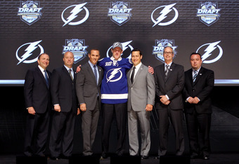 PITTSBURGH, PA - JUNE 22:  Slater Koekkoek (C), tenth overall pick by the Tampa Bay Lightning, poses on stage with general manager Steve Yzerman (3rd L) and team representatives during Round One of the 2012 NHL Entry Draft at Consol Energy Center on June