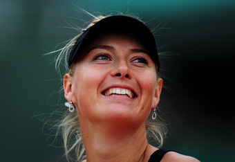 PARIS, FRANCE - JUNE 09:  Maria Sharapova of Russia smiles as she celebrates victory in the women's singles final against Sara Errani of Italy during day 14 of the French Open at Roland Garros on June 9, 2012 in Paris, France.  (Photo by Mike Hewitt/Getty