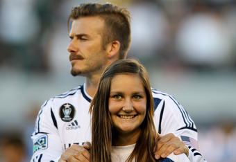 CARSON, CA - JUNE 23:  A youth soccer player smiles as she accompanies David Beckham #23 of the Los Angeles Galaxy during ceremonies before the game with the Vancouver Whitecaps at The Home Depot Center on June 23, 2012 in Carson, California.  The Galaxy