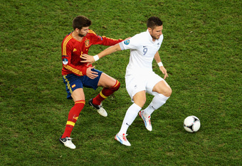 DONETSK, UKRAINE - JUNE 23: Gerard Pique of Spain and Olivier Giroud of France challenge for the ball during the UEFA EURO 2012 quarter final match between Spain and France at Donbass Arena on June 23, 2012 in Donetsk, Ukraine.  (Photo by Jasper Juinen/Ge