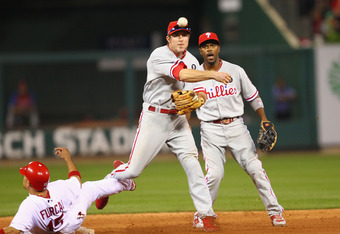 ST. LOUIS, MO - OCTOBER 4: Chase Utley #26 of the Philadelphia Phillies turns an inning-ending double play over Rafael Furcal #15 of the St. Louis Cardinals as Jimmy Rollins #11 also of the Philadelphia Phillies looks on during game three of the National
