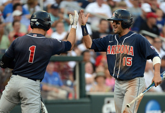 OMAHA, NE - JUNE 25:  Joseph Maggi #15 of the Arizona Wildcats celebrates his run with Johnny Field #1 off of a Trent Gilbert #4 groundout for a 1-0 lead over the South Carolina Gamecocks in the third inning during game 2 of the College World Series at TD