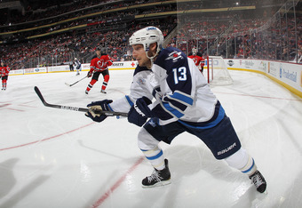 NEWARK, NJ - JANUARY 17:  Kyle Wellwood #13 of the Winnipeg Jets skates against the New Jersey Devils at the Prudential Center on January 17, 2012 in Newark, New Jersey. The Devils defeated the Jets 5-1.  (Photo by Bruce Bennett/Getty Images)