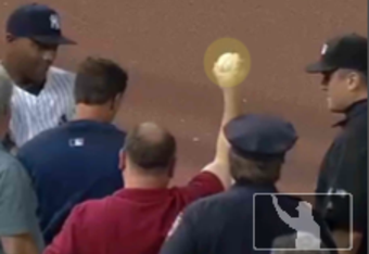 This Umpire Ejection Fantasy League photo shows fan Vinnie Pellegrino clutching Jack Hannahan's 7th inning foul ball. Meanwhile, Yankees outfielder Dewayne Wise has duped umpire Mike DiMuro into calling the out.