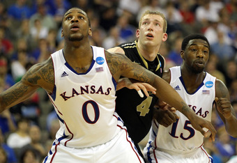 OMAHA, NE - MARCH 18:  Thomas Robinson #0 and Elijah Johnson #15 of the Kansas Jayhawks fight for rebound position in the second half against Robbie Hummel #4 of the Purdue Boilermakers during the third round of the 2012 NCAA Men's Basketball Tournament a