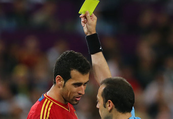 DONETSK, UKRAINE - JUNE 27: Sergio Busquets of Spain is shown the yellow card by referee Cuneyt Cakir during the UEFA EURO 2012 semi final match between Portugal and Spain at Donbass Arena on June 27, 2012 in Donetsk, Ukraine.  (Photo by Martin Rose/Getty