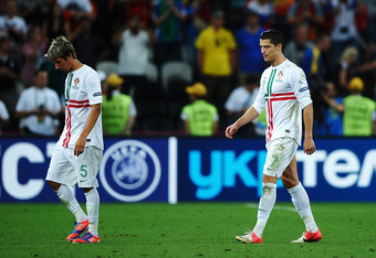 DONETSK, UKRAINE - JUNE 27: Fabio Coentrao and Cristiano Ronaldo of Portugal look dejected after losing a penalty shoot out during the UEFA EURO 2012 semi final match between Portugal and Spain at Donbass Arena on June 27, 2012 in Donetsk, Ukraine.  (Phot