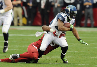 GLENDALE, AZ - JANUARY 01:  Marshawn Lynch #24 of the Seattle Seahawks tries to break a tackle against the Arizona Cardinals at University of Phoenix Stadium on January 1, 2012 in Glendale, Arizona.  (Photo by Norm Hall/Getty Images)