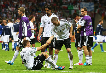 WARSAW, POLAND - JUNE 28:  Bastian Schweinsteiger of Germany helps team-mate Holger Badstuber to his feet as Germany players show their dejection after the UEFA EURO 2012 semi final match between Germany and Italy at the National Stadium on June 28, 2012