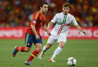 DONETSK, UKRAINE - JUNE 27: Xavi Hernandez of Spain and Miguel Veloso of Portugal in action during the UEFA EURO 2012 semi final match between Portugal and Spain at Donbass Arena on June 27, 2012 in Donetsk, Ukraine.  (Photo by Jasper Juinen/Getty Images)