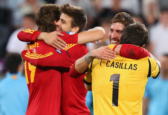 DONETSK, UKRAINE - JUNE 27:  Fernando Llorente of Spain hugs team mate Gerard Pique (L) and Sergio Ramos hugs Iker Casillas after victory during the UEFA EURO 2012 semi final match between Portugal and Spain at Donbass Arena on June 27, 2012 in Donetsk, U