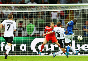 WARSAW, POLAND - JUNE 28:  Mario Balotelli of Italy battles with Philipp Lahm of Germany as he scores his team's second goal past Manuel Neuer of Germany during the UEFA EURO 2012 semi final match between Germany and Italy at the National Stadium on June