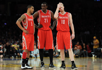 LOS ANGELES, CA - APRIL 06:  Courtney Lee #5, Samuel Dalembert #21 and Chase Budinger #10 of the Houston Rockets wait for the start of play during the game against the Los Angeles Lakers at Staples Center on April 6, 2012 in Los Angeles, California.  NOTE