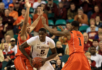 GREENSBORO, NC - MARCH 11:  Bernard James #5 of the Florida State Seminoles looks to pass against Victor Davila #14 and Terrell Bell #1 of the Virginia Tech Hokies during the second half in the quarterfinals of the 2011 ACC men's basketball tournament at