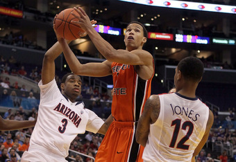 LOS ANGELES, CA - MARCH 10:  Jared Cunningham #1 of the Oregon State Beavers goes up for a shot between Kevin Parrom #3 and Lamont Jones #12 of the Arizona Wildcats in the first half in the quarterfinals of the 2011 Pacific Life Pac-10 Men's Basketball To