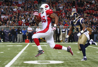 ST. LOUIS, MO - NOVEMBER 27:  Beanie Wells #26 of the Arizona Cardinals breaks free for a 53-yard run against  Quintin Mikell #27 of the St. Louis Rams at the Edward Jones Dome on November 27, 2011 in St. Louis, Missouri.  The Cardinals beat the Rams 23-2