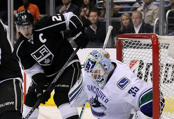 LOS ANGELES, CA - APRIL 15:  Goalie Cory Schneider #35 of the Vancouver Canucks makes a pad save in front of Dustin Brown #23 of the Los Angeles Kings in Game Three of the Western Conference Quarterfinals during the 2012 NHL Stanley Cup Playoffs at Staple