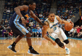 NEW ORLEANS, LA - APRIL 04:  Eric Gordon #10 of the New Orleans Hornets drives the ball around Kenneth Faried #35 of the Denver Nuggets at New Orleans Arena on April 4, 2012 in New Orleans, Louisiana.  NOTE TO USER: User expressly acknowledges and agrees