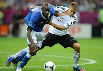 WARSAW, POLAND - JUNE 28:  Mario Balotelli of Italy battles for the ball with  Holger Badstuber of Germany during the UEFA EURO 2012 semi final match between Germany and Italy at the National Stadium on June 28, 2012 in Warsaw, Poland.  (Photo by Christop