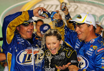 SPARTA, KY - JUNE 30:  Crew members for Brad Keselowski, driver of the #2 Miller Lite Dodge, celebrate with Miss Sprint Kim Coon in Victory Lane after Keselowski won the NASCAR Sprint Cup Series Quaker State 400 at Kentucky Speedway on June 30, 2012 in Sp
