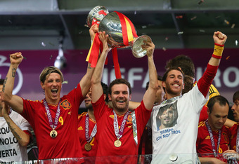 KIEV, UKRAINE - JULY 01: (L-R) Fernando Torres, Juan Mata and Sergio Ramos of Spain lift the trophy after victory during the UEFA EURO 2012 final match between Spain and Italy at the Olympic Stadium on July 1, 2012 in Kiev, Ukraine.  (Photo by Handout/UEF