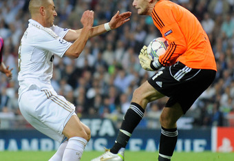 MADRID, SPAIN - OCTOBER 18: Karim Benzama (L) of Real Madrid challenges Hugo Lloris of Olympique Lyonnais during the UEFA Champions League Group D match between Real Madrid CF and Olympique Lyonnais at Estadio Santiago Bernabeu on October 18, 2011 in Madr