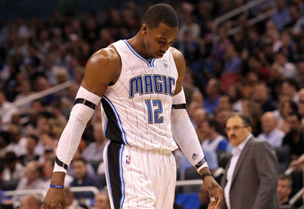 ORLANDO, FL - MARCH 13:  Dwight Howard #12 of the Orlando Magic walks off the court during the game against the Miami Heat at Amway Center on March 13, 2012 in Orlando, Florida.  NOTE TO USER: User expressly acknowledges and agrees that, by downloading an