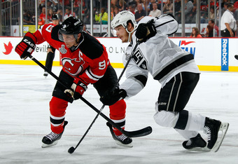 NEWARK, NJ - JUNE 09:  Dustin Brown #23 of the Los Angeles Kings skates with the puck against Zach Parise #9 of the New Jersey Devils during Game Five of the 2012 NHL Stanley Cup Final at the Prudential Center on June 9, 2012 in Newark, New Jersey.  (Phot