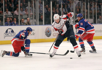 NEW YORK, NY - APRIL 30:  Alexander Semin #28 of the Washington Capitals attempts to control the puck in the first period againnst Derek Stepan #21 and Brad Richards #19 of the New York Rangers in Game Two of the Eastern Conference Semifinals during the 2
