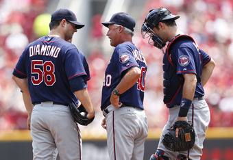 CINCINNATI, OH - JUNE 24: Scott Diamond #58 of the Minnesota Twins talks with pitching coach Rick Anderson after hitting his second batter in a row in the third inning during an interleague game against the at Great American Ball Park on June 24, 2012 in