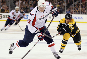 BOSTON, MA - APRIL 25: Alexander Semin #28 of the Washington Capitals takes a shot as Andrew Ference #21 of the Boston Bruins defends in Game Seven of the Eastern Conference Quarterfinals during the 2012 NHL Stanley Cup Playoffs at TD Garden on April 25,
